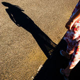 Shadow of a female figure. On the asphalt road Royalty Free Stock Photos
