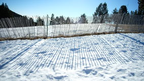 Shadow of fence in the snow Royalty Free Stock Photography