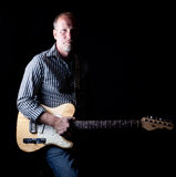 Shadow filled shot a rugged looking guitar player Royalty Free Stock Photography