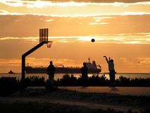 Shadow game. Kids playing basketball on the beach during the sunset; big cargo boat on background Stock Photo