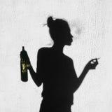 Shadow of girl smoking around on wall background Stock Photo