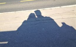 Shadow on the grey concrete of two people sitting on a bench stock image