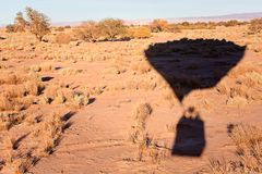 Hot air ballooning. Shadow on the ground of flying hot air balloon in atacama desert, chile, adventure vacation concept Stock Images