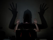 Shadow hacker in the dark. A masked hacker hiding his face with a black scarf and trying to crack a online site in the dark. Big shadow reflects on the dark wall Royalty Free Stock Photo