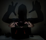 Shadow hacker in the dark. A masked hacker hiding his face with a black scarf and trying to crack a online site in the dark. Big shadow reflects on the dark wall Stock Photos
