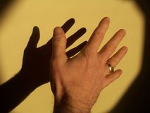 Shadow of a hand. Photo of a hand with shadow on the wall Royalty Free Stock Photography