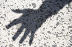 Shadow of hand against pavement Stock Photography