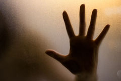 Shadow of hand behind wet glass. Stock Image