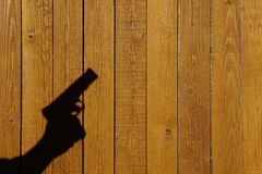 Shadow of a hand with a gun on a wooden fence. With space for text or image Royalty Free Stock Images