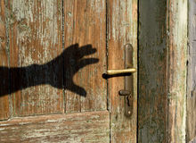Shadow of hand and old door Stock Photography