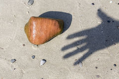 Shadow of a hand and pebble at the beach Royalty Free Stock Images