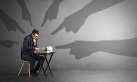 Shadow hands pointing at a small worker Stock Photos