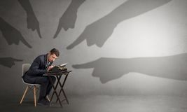 Shadow hands pointing at a small worker Stock Image