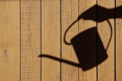 The shadow of a hand with watering can Stock Images