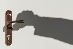 Shadow of hands on the door handle Stock Photos