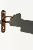 Shadow of hands on the door handle Stock Photography