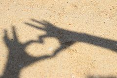 Shadow hands making heart icon on sand at the beach. Shadow hands is making heart icon on sand at the beach stock image