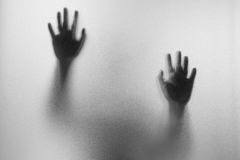 Shadow hands of the Man behind frosted glass.Blurry hand abstrac. Tion.Halloween background.Black and white picture royalty free stock photography