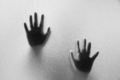 Shadow hands of the Man behind frosted glass.Blurry hand abstrac. Tion.Halloween background.Black and white picture Royalty Free Stock Image