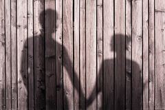 Happy couple holding hands together. Shadow of happy couple holding hands together in the sunset stock image