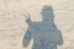 Shadow of a happy person resting on a sandy beach. Summer rest.  stock image