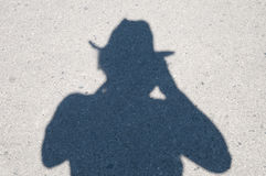 Shadow in the Hat. Shadow on the pavement from the man in the hat Stock Photo