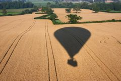 The Shadow of a hot air balloon flying over rural farmland. Shadow of a hot air balloon flying over rural farmland Royalty Free Stock Photo