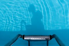 Shadow of human body in a swimming pool at ladder. Photo of a human body shadow in a swimming pool at ladder royalty free stock photos