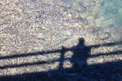 Shadow of an individual on a bridge looking at the water.  Stock Photos