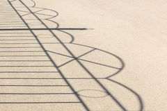 The shadow of the iron-wrought fence on asphalt stock image