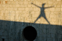 Shadow jumping on the wall. Meaning great success and happy Royalty Free Stock Photography