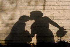 The shadow of kissing newlyweds on wooden background royalty free stock image