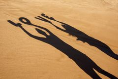 Shadow of letters forming the word love. Closeup of the shadow of a man and a woman holding some letters forming the word love over their heads on the sand of a Royalty Free Stock Image