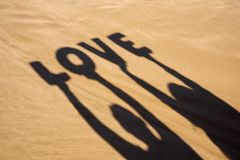 Shadow of letters forming the word love. Closeup of the shadow of a man and a woman holding some letters forming the word love over their heads on the sand of a Stock Photo