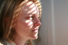 Shadow and Light. A beautiful young woman looks out a window Royalty Free Stock Photography