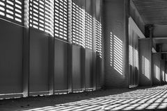 Shadow and light. Black and white. Sunny day light from metal lattice in abandoned unfinished shoping mall. Shadow and light. Black and white. Sunny light from Stock Images