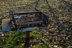 Shadow and light with grill. Old grill filling with leaves in early winter Royalty Free Stock Photography
