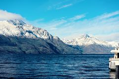 Lake Wakatipu Near Queenstown In New Zealand. Shadow and light on Lake Wakatipu near Queensland in New Zealand with The Remarkables mountain range in the stock photos