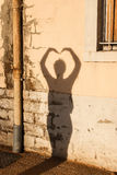 Shadow making a heart shape against a wall. A silhouette of a woman making a heart shape with her hands against a wall stock photos
