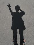 Shadow of a man. With a raised hand on the gray asphalt Stock Photos