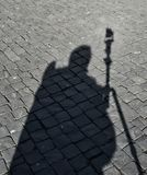 Shadow man, abstract black-and-white image of shadow on cobblestones, abstract stock photography