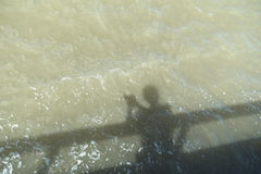 Shadow of man cast on water. Shadow of man at railing cast on water Royalty Free Stock Photo
