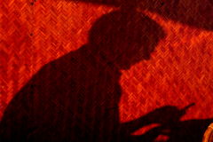 Shadow of a man. A cell phone texting person's shadow behind textured wall Stock Photos