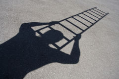 Shadow of man climbing ladder. On asphalt Royalty Free Stock Photo