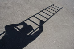 Shadow of man climbing ladder. On asphalt Royalty Free Stock Images