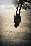Shadow of a man crossing the street. Shadow of a tired man crossing the street in Paris, France Stock Photography