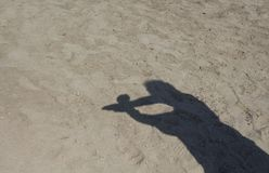 Shadow of man doing handcuffed sign. On sand background in Cunda / Turkey Royalty Free Stock Image