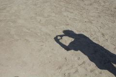 Shadow of man doing love sign on sand background. Shadow of man doing love sign on sand background in Bodrum Turkey Royalty Free Stock Image