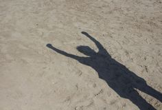 Shadow of man doing socialism sign. On sand background. Raised fist is a symbol of solidarity and support. It is also used as a salute to express unity stock photo