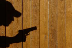 Shadow of a man with a gun on a wooden fence Stock Photos